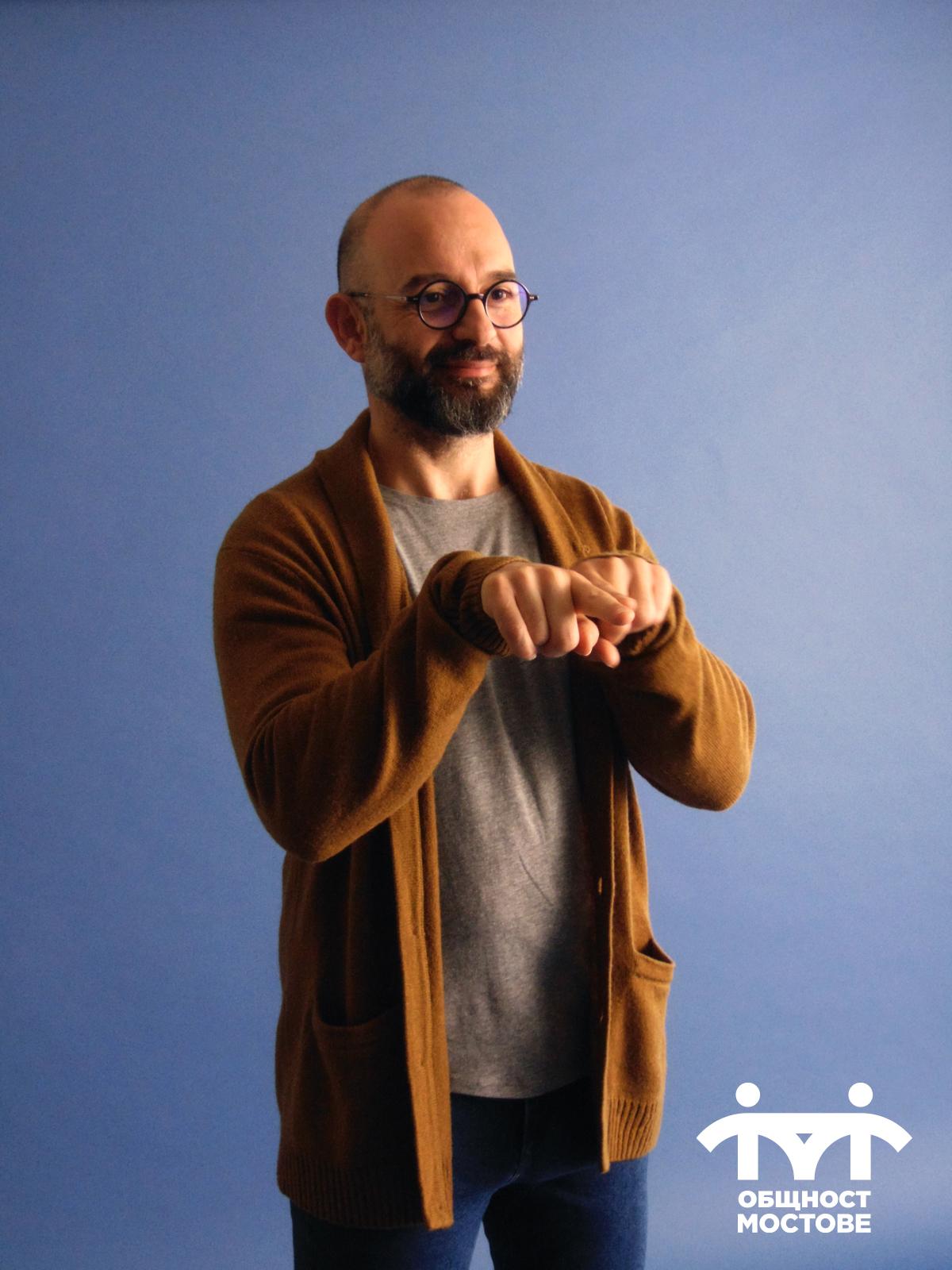 Част от снимачния ден. Ашод на син фон, показва знаци от българския жестов език.