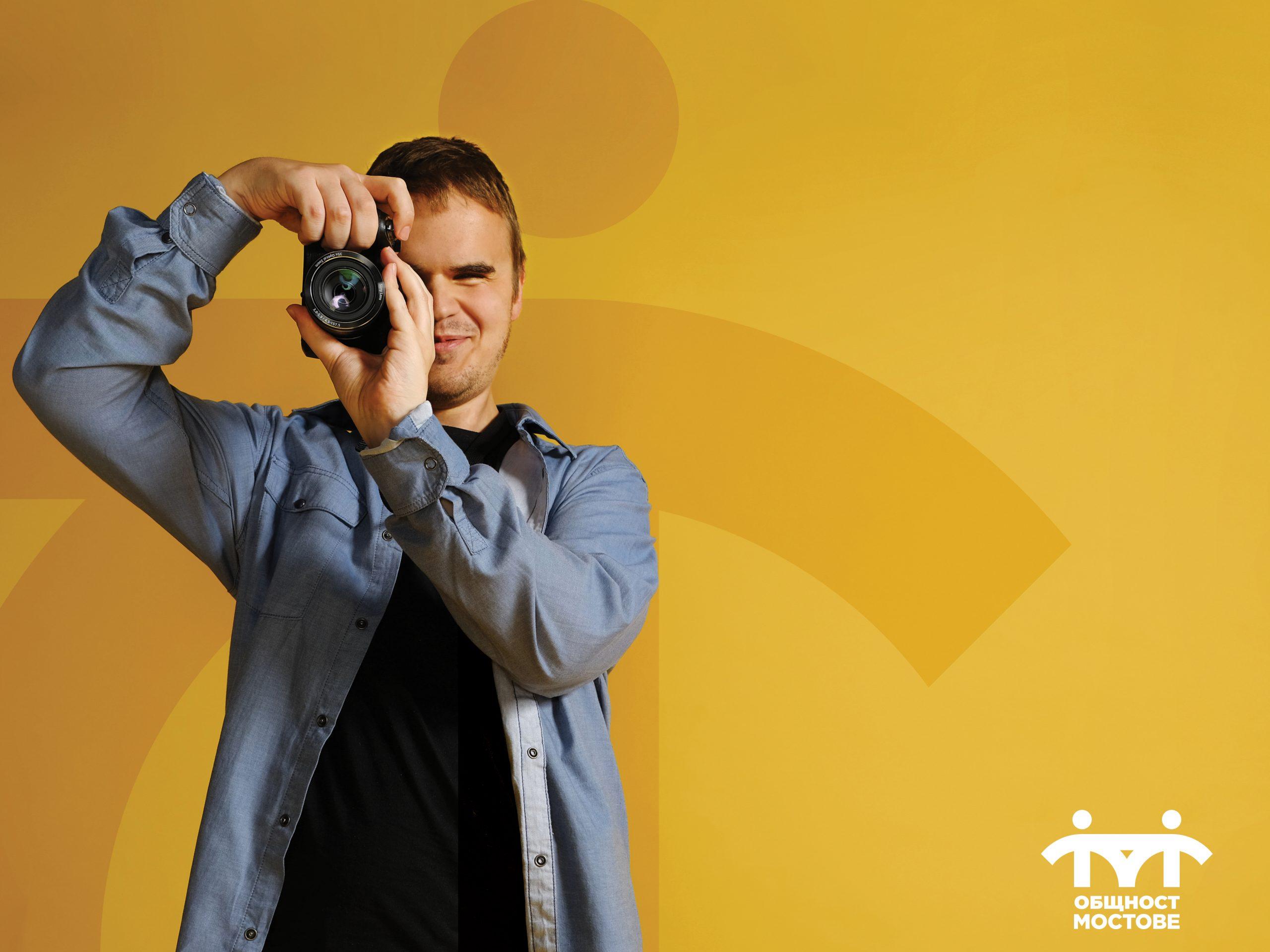 Дилиян, фокусиращ с фотоапарат на жълт фон.